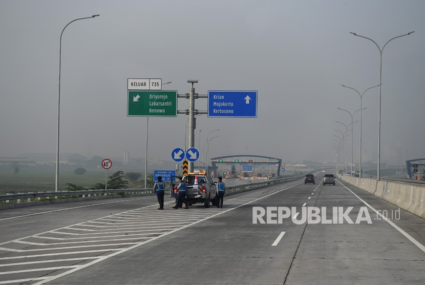 Sejumlah petugas mengatur kendaraan melintasi jalan Tol Surabaya Mojokerto saat penyusuran pra uji laik fungsi dan keselamatan Trans Jawa, Gresik, Jawa Tengah, Jumat (7/12/2018).