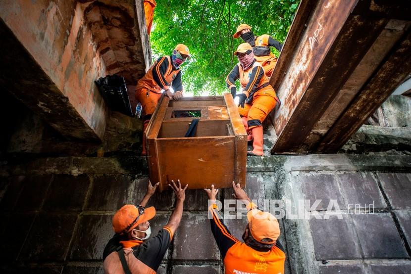 Sejumlah petugas PPSU mengangkut lemari saat menertibkan hunian liar di kolong jembatan Jalan Proklamasi, Pegangsaan, Menteng, Jakarta, Selasa (29/12/2020). Sebanyak 12 hunian liar ditertibkan oleh petugas dari Kelurahan Pegangsaan, setelah sebelumnya Menteri Sosial Tri Rismaharini melakukan sidak di kolong jembatan tersebut.