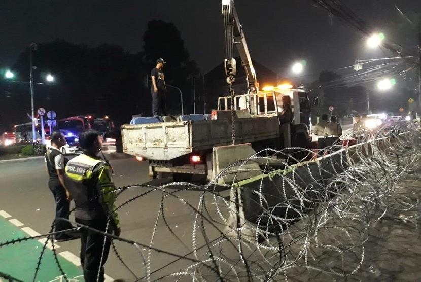Sejumlah petugas sedang memasang separator beton di Jalan Imam Bonjol, depan kantor KPU, Selasa (21/5) dinihari.