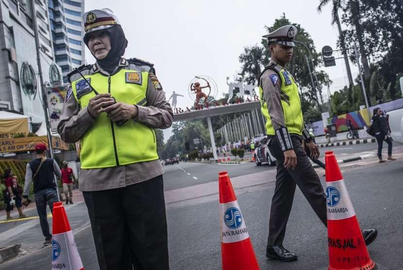 Sejumlah Polisi lalu-lintas melakukan penjagaan saat dilakukan penutupan jalan di kawasan Gelora Bung Karno (GBK), Senayan, Jakarta, Sabtu (18/8).
