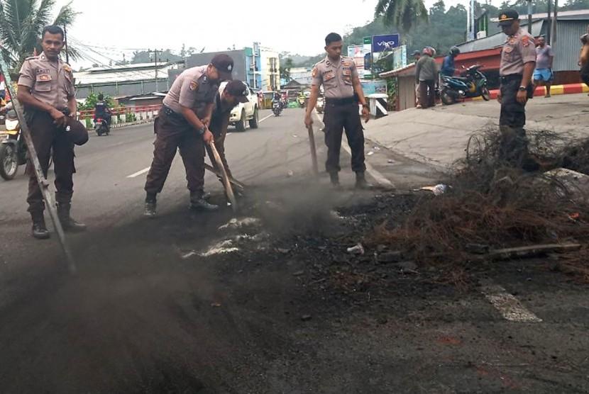 Sejumlah polisi membersihkan sisa kerusuhan di salah satu ruas jalan di Manokwari, Papua Barat, Selasa (20/8/2019).