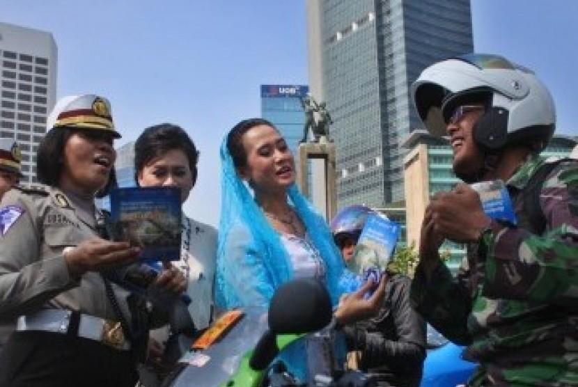 Sejumlah Polisi Wanita (Polwan) memakai Kebaya membagikan Brosur sosialisasi Undang-undang Lalu lintas kepada pengendara bermotor dalam memperingati Hari Kartini di kawasan MH. Thamrin, Jakarta, Kamis (21/4).