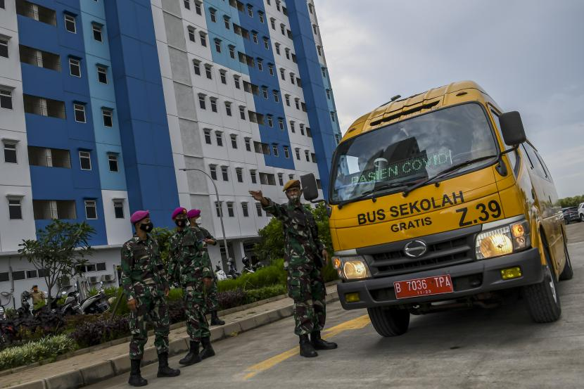 Prajurit TNI mengarahkan bus sekolah yang mengangkut pasien Covid-19 memasuki Rusun Nagrak di Kecamatan Cilincing, Jakarta Utara.
