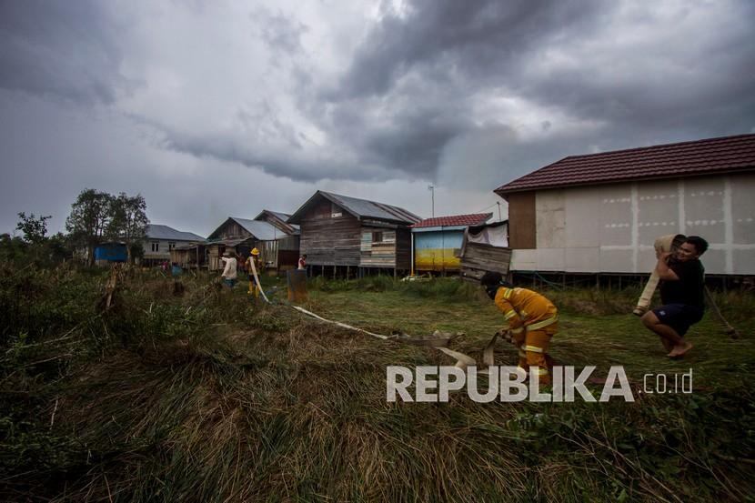 Sejumlah relawan berupaya memadamkan kebakaran lahan yang sudah mendekati permukiman warga di Kecamatan Liang Anggang, Banjarbaru, Kalimantan Selatan, Selasa (21/9/2021). Kencangnya angin di lokasi kebakaran lahan membuat api dengan cepat menyebar yang diperkirakan mencapai puluhan hektare, dan hingga kini BPBD Kota Banjarbaru dibantu relawan pemadam kebakaran Kota Banjarmasin masih berupaya memadamkan api yang mendekati permukiman penduduk di daerah setempat.