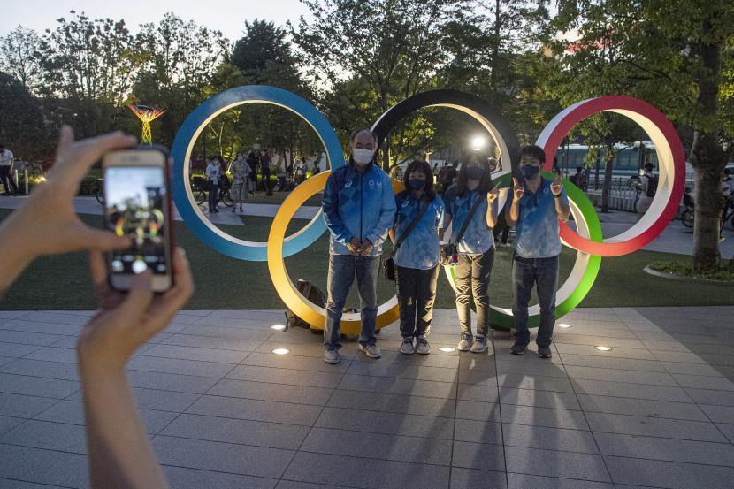 Sejumlah relawan Olimpiade Tokyo 2020 berfoto bersama di kawasan Stadion Nasional, Tokyo, Jepang, Kamis (22/7/2021).