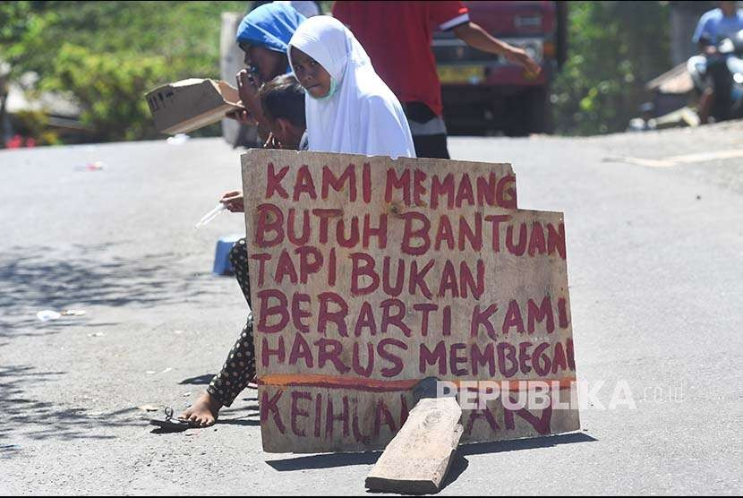 Sejumlah remaja pengungsi korban gempa bumi meminta bantuan di tengah jalan di sekitar lokasi tempat pengungsian darurat di Kayangan, Lombok Utara, NTB, Minggu (12/8). Masih terdapat pengungsi yang belum mendapat bantuan karena sulitnya akses untuk menjangkau lokasi pengungsi.