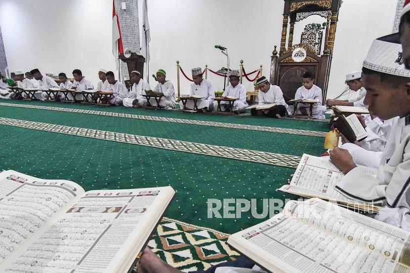 Sejumlah santri membaca Al-Quran di Pesantren Nuu Waar Al Fatih Kaffah Nusantara (AFKN) di Setu, Kabupaten Bekasi, Jawa Barat, Sabtu, (24/4/2021). Kegiatan Khatam Al-Quran tersebut dilakukan rutin setiap bulan Ramadhan oleh 750 santri dan santriwati.
