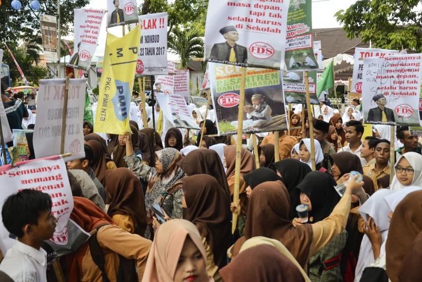 Santri membawa poster saat berunjuk rasa menolak kebijakan aturan full day school (Ilustrasi)