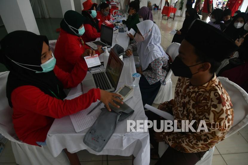Kemenkes Targetkan Vaksinasi di Atas 20 Persen September. Sejumlah santri mengikuti pelaksanaan vaksinasi massal COVID-19 untuk santri atau pelajar di Komplek PB Alkhairaat Palu di Palu, Sulawesi Tengah, Kamis (23/9/2021). Vaksinasi massal yang dilaksanakan oleh Badan Intelijen Negara (BIN) dengan menggandeng Pondok Pesantren Alkhairaat Pusat Palu tersebut menargetkan pemberian vaksin COVID-19 kepada 3.000 orang santri. Pelaksanaan vaksinasi itu sebagai upaya pemerintah menjadikan pandemi COVID-19 menjadi endemi serta mendukung pelaksanaan pembelajaran tatap muka yang akan segera dilaksanakan di daerah tersebut.