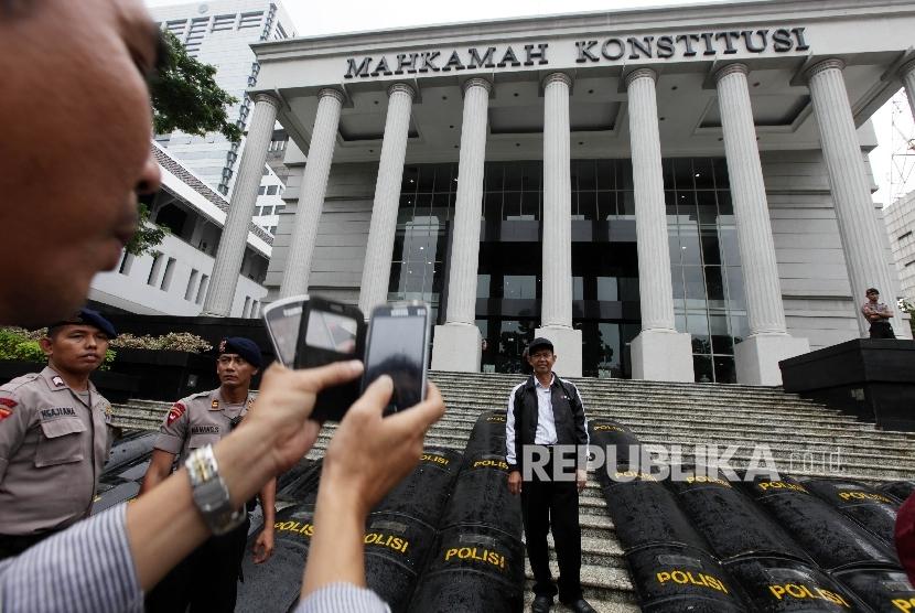 Sejumlah simpatisan asal daerah berfoto didepan gedung Mahkakamah Konstitusi (MK) saat berlangsungnya sidang panel lanjutan perselisihan hasil pemilihan (PHP) kepala daerah 2015 di Gedung Mahkamah Konstitusi, Jakarta, Kamis (21/1).