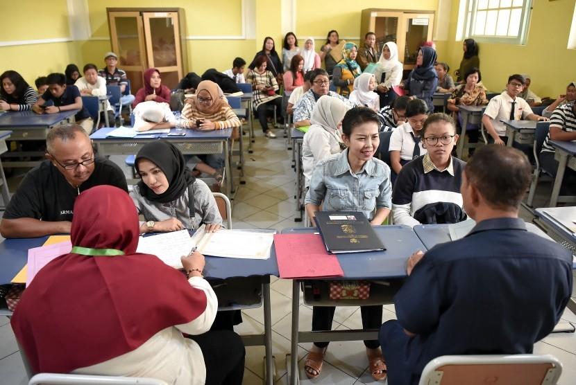 Sejumlah siswa dan orang tua murid antre mengikuti seleksi Penerimaan Peserta Didik Baru (PPDB) di SMAN 1 Jakarta, Jakarta, Senin (24/6/2019).
