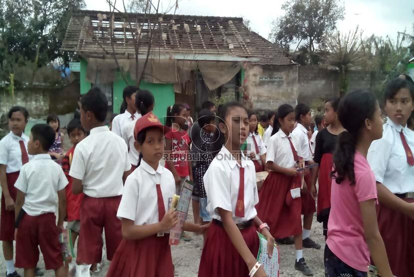 Sejumlah siswa SDN 03 Puncu kembali ke sekolah, setelah sempat diliburkan pascaerupsi gunung Kelud, Senin (24/2