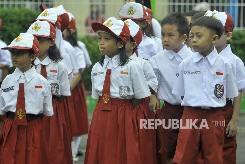 Sejumlah siswa-siswi murid baru kelas 1 mengikuti apel pada hari pertama masuk sekolah di Sekolah Dasar Negeri (SDN) Pejaten Barat 10 Pagi, Jakarta Selatan, Senin (10/7).
