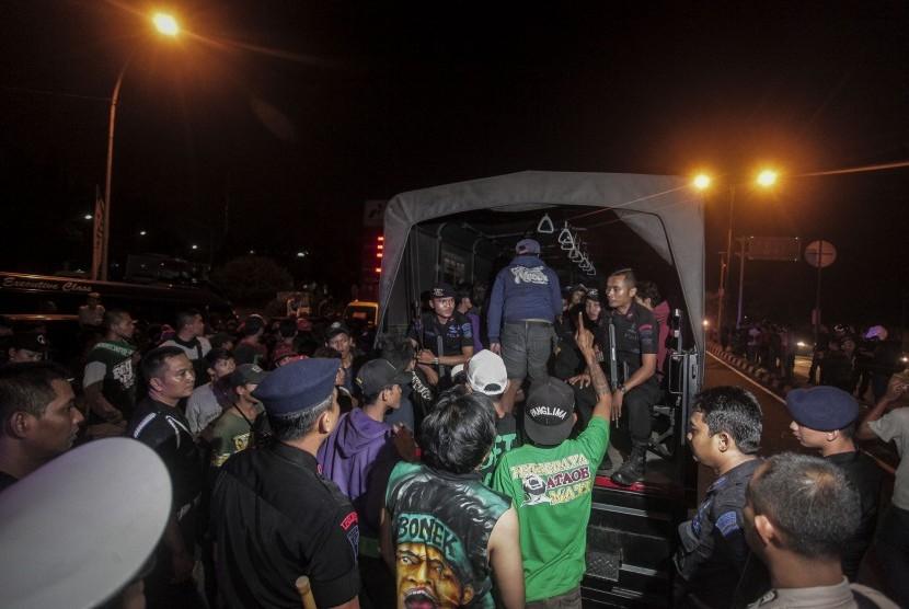 Sejumlah suporter Persebaya, Bonek menaiki truk Polisi saat pemulangan Bonek di kawasan Giwangan, Yogyakarta, Minggu (3/6). Polda DI Yogyakarta menerjunkan sejumlah truk dan ratusan personil guna memfasilitasi pemulangan Bonek menyusul dibatalkannya pertandingan sepak bola antara Persija melawan Persebaya yang dijadwalkan bertanding di Stadion Sultan Agung, Bantul pada Ahad (3/6) malam, akibat terjadinya kerusuhan antaroknum suporter Persebaya dan Persija sebelum pertandingan.