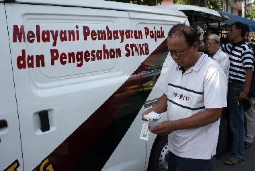 Sejumlah warga antri mengurus perpanjangan Surat Tanda Nomor Kendaraan (STNK) dengan memanfaatkan fasilitas mobil