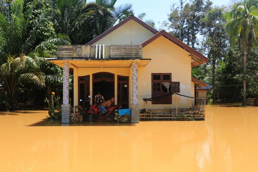 Sejumlah warga berada di depan rumahnya yang terendam banjir di Desa Blang Luah, Woyla Timur, Aceh Barat, Aceh, Sabtu (15/5/2021). Banjir yang disebabkan tingginya intensitas hujan dan meluapnya sungai krueng Woyla itu mengakibatkan puluhan rumah warga di Kecamatan Woyla Barat dan Woyla Timur terendam banjir dengan ketinggian air 30-130 cm.