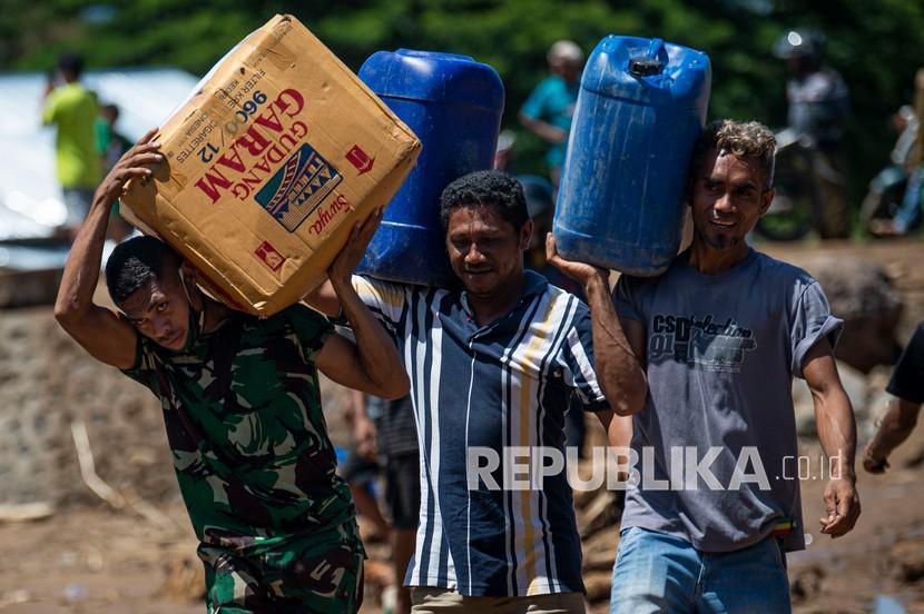 Sejumlah warga bergotong royong memindahkan bantuan logistik dari sejumlah lembaga dan pemerintah untuk korban banjir bandang di Adonara Timur, Kabupaten Flores Timur, Nusa Tenggara Timur (NTT), Rabu (7/4/2021). Bencana alam yang melanda pada Minggu (4/4) tersebut mengakibatkan puluhan orang meninggal dunia dan ratusan warga mengungsi.