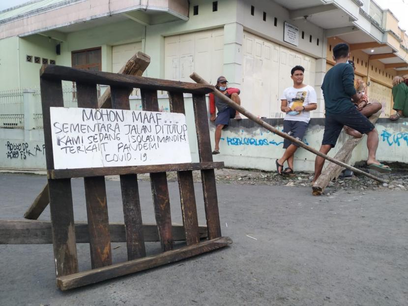 Sejumlah warga berjaga di akses jalan masuk ke Kampung Sambongpari Kidul, Kelurahan Sambongpari, Kecamatan Mangkubumi, Kota Tasikmalaya, Ahad (20/6). Akses ke kampung itu ditutup warga lantaran ada belasan orang yang terkonfirmasi positif Covid-19.