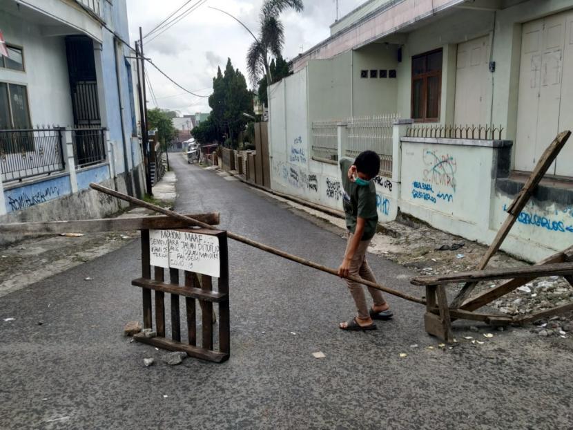 Sejumlah warga berjaga di akses masuk ke Kampung Sambongpari Kulon dan Sambongpari Kidul, Kelurahan Sambongpari, Kecamatan Mangkubumi, Kota Tasikmalaya, Senin (21/6). Askes masuk ke kampung itu dibatasi lantaran adanya belasan warga yang terkonfirmasi positif Covid-19.