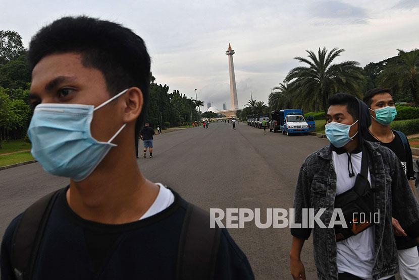 Sejumlah warga dengan menggunakan masker berjalan-jalan di Monumen Nasional. Polres Cianjur, Jawa Barat, menetapkan tiga orang pegawai RSUD Pagelaran-Cianjur dan satu orang penadah sebagai tersangka hilangnya ratusan kotak masker
