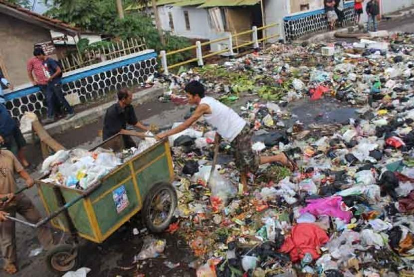 Sejumlah warga melakukan aksi dengan menumpahkan sampah ke Jalan Ciwalen, Kabupaten Garut, Jawa Barat, Jumat (15/11).