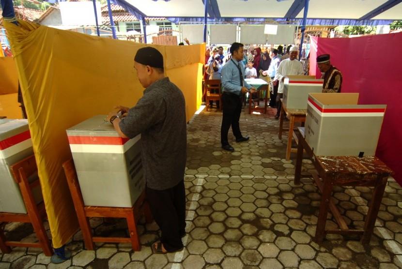 Sejumlah warga melakukan pencoblosan di Tempat Pemungutan Suara (TPS) saat Pemilihan Kepala Desa (Pilkades) serentak 2018 di Desa Danawarih, Kabupaten Tegal, Jawa Tengah, Senin (17/12/2018).