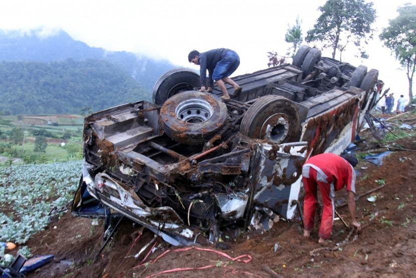 Sejumlah warga melihat bus yang jatuh akibat terlibat kecelakaan beruntun di Jalan Puncak, Ciloto, Cipanas, Cianjur, Jawa Barat, Minggu (30/4).