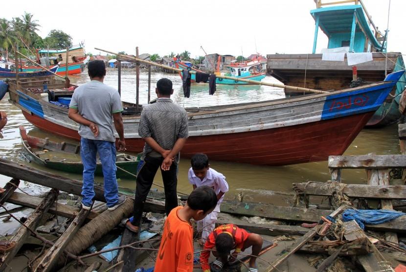 Sejumlah warga melihat perahu milik warga etnis Rohingya yang terdampar di Pelabuhan Kuala Idi Rayeuk, Aceh Timur, Aceh, Selasa (4/12/2018).