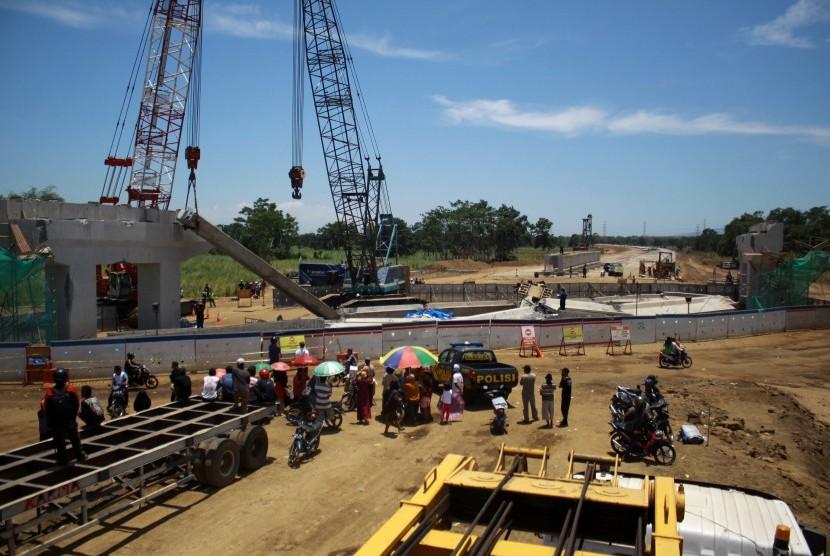 Sejumlah warga melihat tim Laboratorium Forensik Polda Jatim melakukan penyelidikan di lokasi girder proyek Strategis Nasional (PSN) Tol Pasuruan - Probolinggo (Paspro) yang ambruk di Desa Cukurgondang, Grati, Pasuruan, Jawa Timur, Senin (30/10).