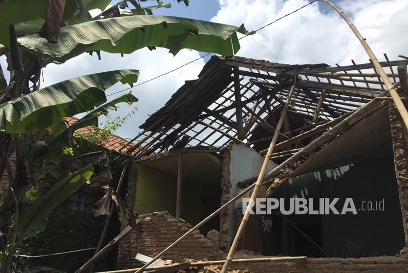 Sejumlah warga melintas di depan rumah yang roboh akibat hujan dan  angin kencang pada Senin (7/1) sore.