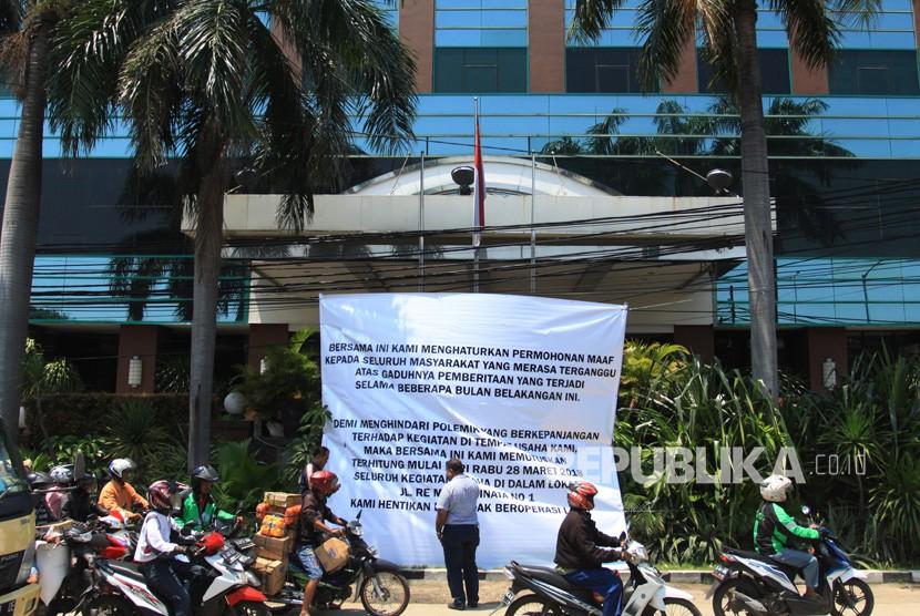 Sejumlah warga melintas di depan spanduk pengumuman penghentian operasional Hotel Alexis di Jalan RE Martadinata, Jakarta, Rabu (28/3).