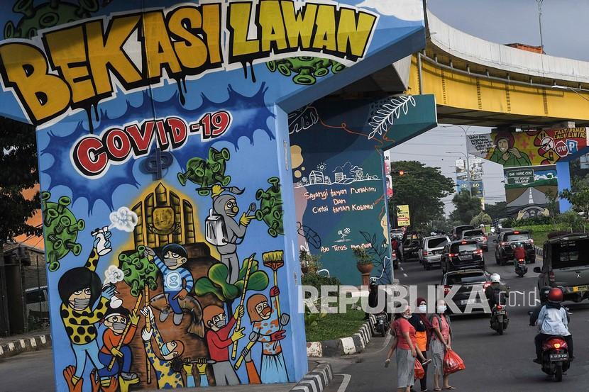 Sejumlah warga melintas disamping mural bertemakan sosialisasi untuk mencegah wabah COVID-19, Bekasi, Jawa Barat, Kamis (28/1/2021). Pemerintah Kota Bekasi memperpanjang Pemberlakuan Pembatasan Kegiatan Masyarakat (PPKM) hingga 30 hari untuk menurunkan kasus positif COVID-19.