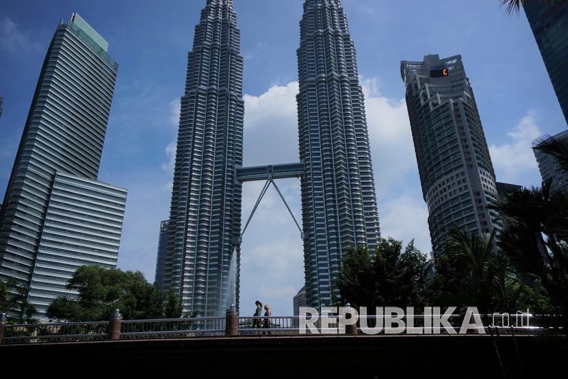 Malaysia akan Batasi Pekerja Asing Maksimal 15 Persen. Sejumlah warga melintas pada sebuah jembatan di area Kuala Lumpur Convention Center (KLCC) Park dengan latar belakang Menara Kembar Petronas, di Kuala Lumpur.