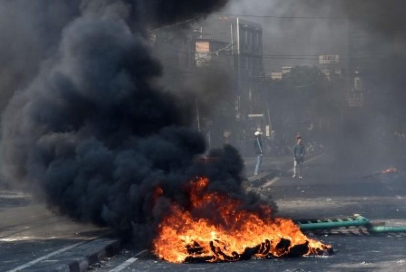 Sejumlah warga melintasi ban yang dibakar di tengah Jalan KS. Tubun, Petamburan, Jakarta Pusat, Rabu (22/5/2019).