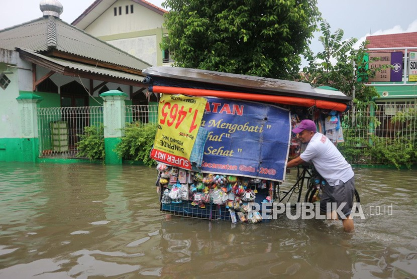 Sejumlah warga melintasi jalan yang terimbas banjir di wilayah Kelurahan Duren Jaya Kecamatan Bekasi Timur Kota Bekasi, Kamis (15/2).