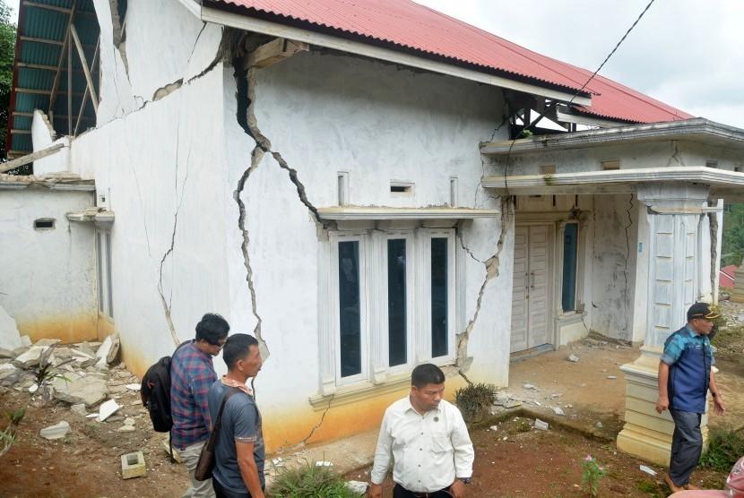 Gempa Solok: Sejumlah warga memperhatikan rumah yang rusak akibat gempa di Kabupaten Solok Selatan, Sumatera Barat, Kamis (28/2/2019).