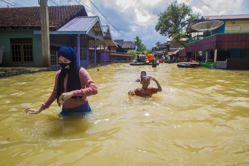Sejumlah warga menerobos banjir yang merendam permukiman di Jalan Biduri, Kecamatan Satui, Kabupaten Tanah Bumbu , Kalimantan Selatan, Sabtu (15/5/2021). BPBD Kabupaten Tanah Bumbu mencatat sebanyak 2.126 unit rumah di Kecamatan Satui tersebut terendam banjir setinggi 50 cm hingga dua meter akibat tingginya intensitas curah hujan yang mengakibatkan meluapnya Sungai Satui.