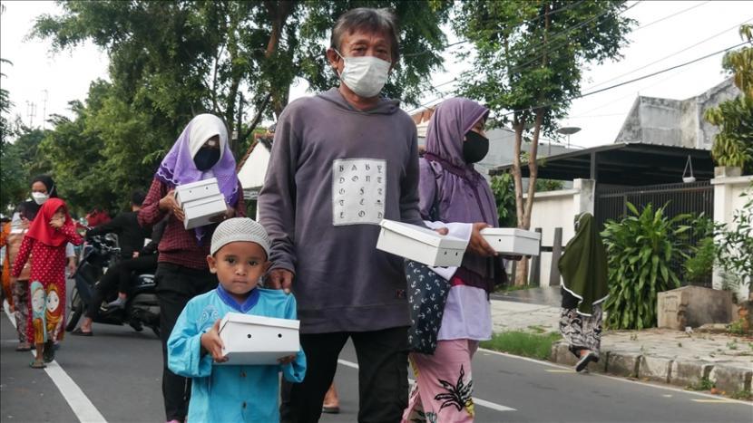Sejumlah warga mengantre dan menjaga jarak sosial sebagai bagian pencegahan penyebaran virus korona (Covid-19) untuk mendapatkan makanan berbuka puasa di Cempaka Putih di Jakarta, Indonesia pada 16 April, 2021.