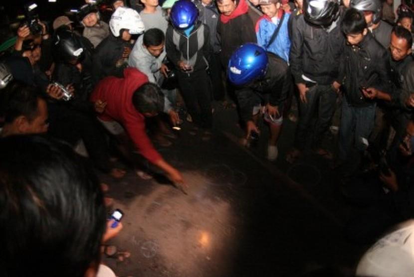 Sejumlah warga mengerubuti percikan darah yang telah ditutupi pasir di lokasi baku tembak antara Densus 88 dengan terduga teroris di Jl Veteran, Tipes, Solo, Jumat (31/8) malam.