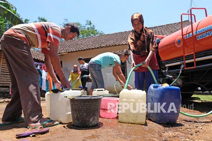 Sejumlah warga mengumpulkan air saat penyaluran air bersih di daerah krisis air bersih selama musim kemarau.