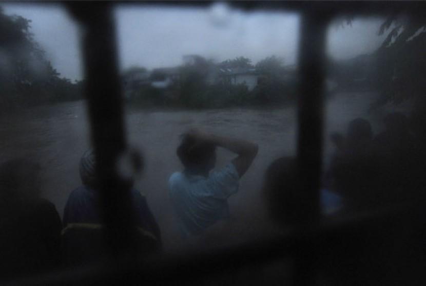 Sejumlah warga menonton banjir yang melanda bantaran sungai Ciliwung di kawasan Kampung Melayu, Jakarta, Selasa (15/1).