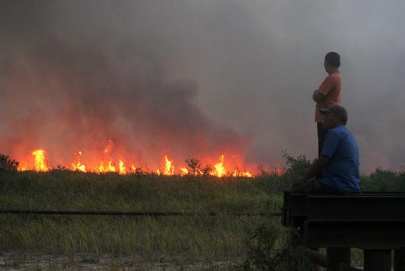 Sejumlah warga menyaksikan kobaran api di lahan gambut di Kecamatan Bangko Pusako Kabupaten Rokan Hilir, Riau, Sabtu (22/6).