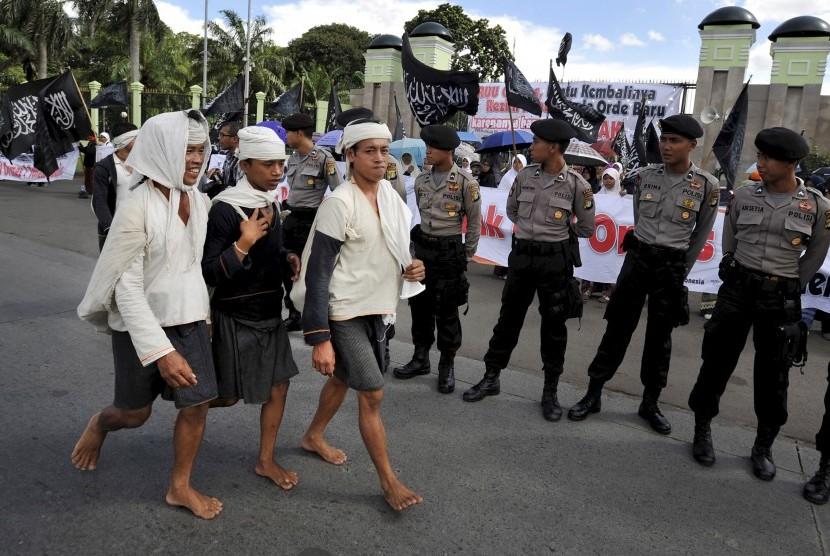 Sejumlah warga suku badui berjalan kaki ketika menjual hasil kerajinan dan hasil bumi khas Badui di Jakarta.