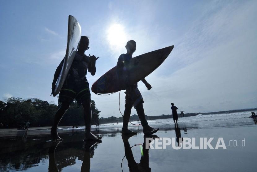 Sejumlah wisatawan berjalan dengan membawa papan surfing di Pantai Batu Karas, Kabupaten Pangandaran, Jawa Barat, Rabu (17/8). (Mahmud Muhyidin)