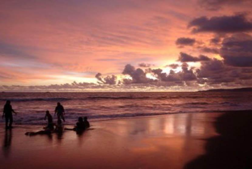 Sejumlah wisatawan bermain air saat matahari terbenam di pantai Palabuhanratu, Sukabumi, Jawa Barat.