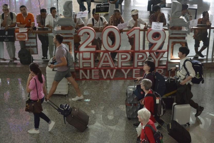 Sejumlah wisatawan membawa barang milik mereka setibanya di Bandara Internasional I Gusti Ngurah Rai, Bali, Kamis (27/12).