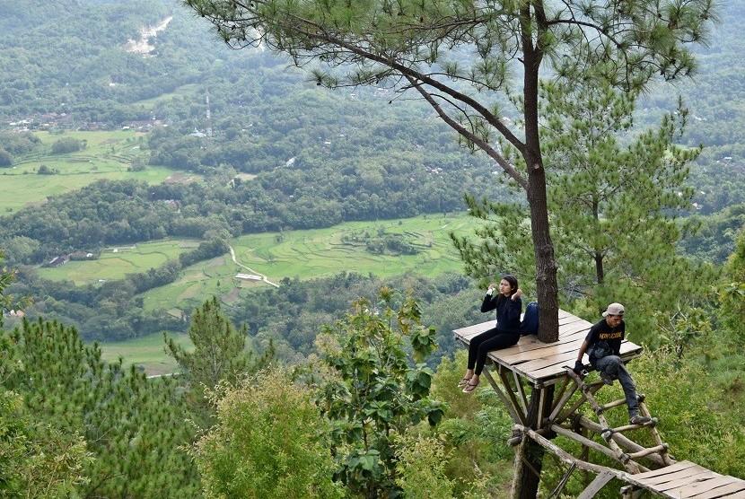 Sejumlah wisatawan menikmati panorama Yogyakarta dari ketinggian di obyek wisata alam Puncak Becici di kawasan Hutan Mangunan, Dlingo, Bantul, DI Yogyakarta, Rabu (10/5).