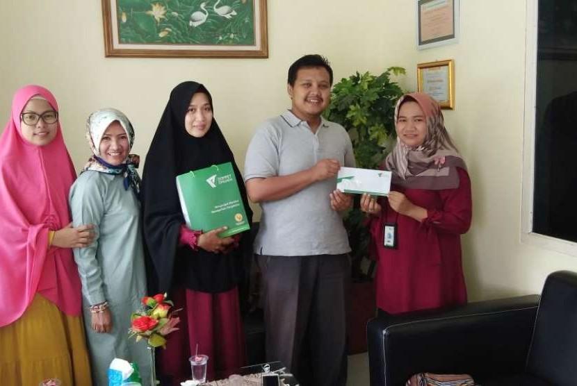 Sekolah Prestasi Global menyerahkan donasi untuk korban gempa Palu kepada Dompet Dhuafa.