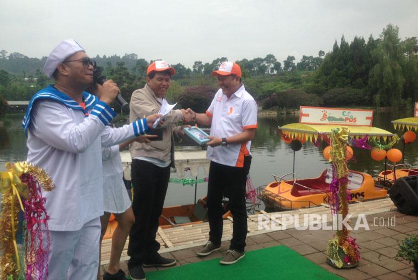 Sekretaris Perusahaan PT Pos Indonesia, Hairul Syafiudin serah terima piagam dengan Owner Floating Market Perry Tristianto di Kawasan Floating Market Lembang, Ahad (26/3).