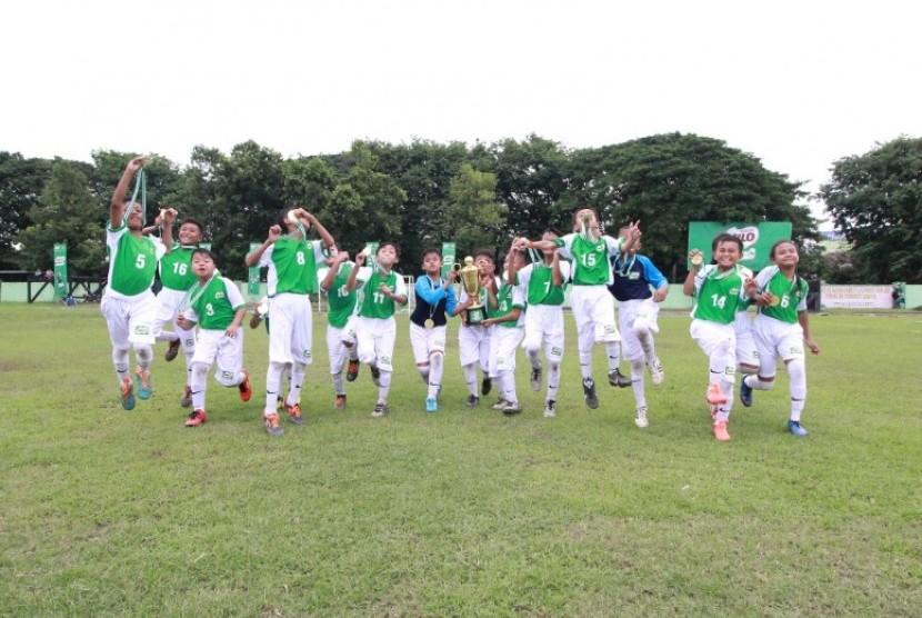 Selebrasi para pemain SDN Bandung Rejosari 1 Malang setelah tampil sebagai juara Milo Football Championship Surabaya 2019